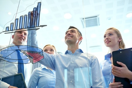 young entrepreneurs: business, people, teamwork and planning concept - smiling business team drawing chart on notice board in office Stock Photo