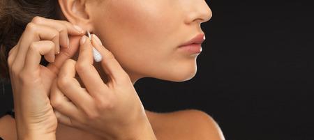 close up of beautiful woman wearing shiny diamond earrings photo