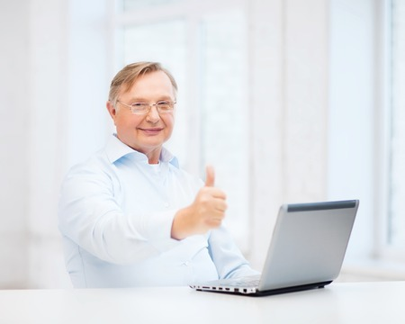 oldness: technology, oldness and lifestyle concept - old man in eyeglasses with laptop computer at home showing thumbs up