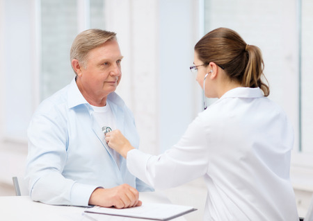heart sounds: healthcare, medicine and elderly concept - female doctor or nurse with old man listening to heart beat Stock Photo