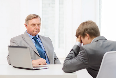 dismiss: business, technology and office concept - older man and young man having argument in office Stock Photo