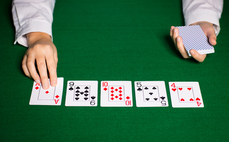 casino, gambling, poker, people and entertainment concept - close up of holdem dealer hands with playing cards