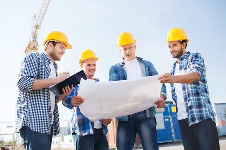ビジネス、建築、チームワークと人コンセプト - クリップボードと屋外の青写真と hardhats 笑顔建設業者のグループ