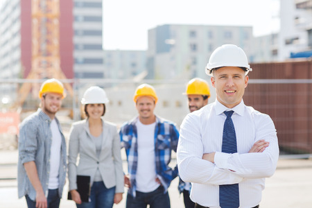 house worker: business, building, teamwork and people concept - group of smiling builders in hardhats outdoors