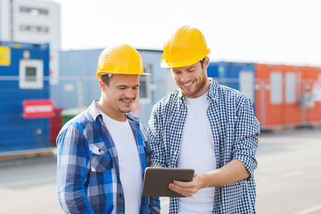 industrial site: business, building, teamwork, technology and people concept - group of smiling builders in hardhats with tablet pc computer outdoors Stock Photo