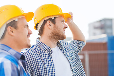 site: business, building, teamwork and people concept - group of smiling builders in hardhats with clipboard outdoors Stock Photo