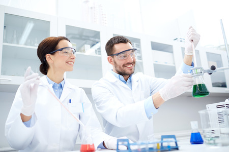 scientists: science, chemistry, technology, biology and people concept - young scientists with pipette and flask making test or research in clinical laboratory