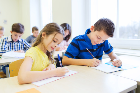 examination: education, elementary school, learning and people concept - group of school kids with pens and notebooks writing test in classroom