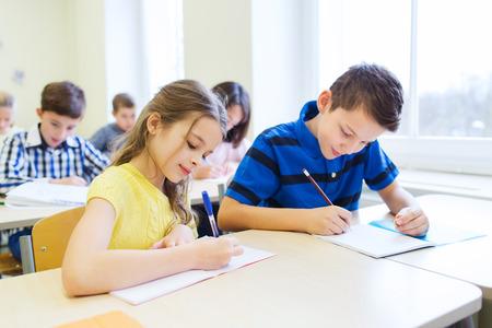 scuola: educazione, scuola elementare, l'apprendimento e la gente concetto - gruppo di ragazzi della scuola con penne e quaderni di scrittura di test in classe