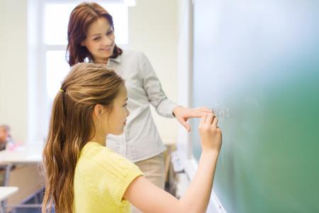 persona escribiendo: educaci�n, escuela primaria, el aprendizaje, las matem�ticas y la gente concepto - peque�o sonriente escribir n�meros colegiala en tarjeta de tiza verde en el aula Foto de archivo