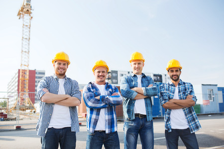 construction house: business, building, teamwork and people concept - group of smiling builders in hardhats with clipboard outdoors Stock Photo
