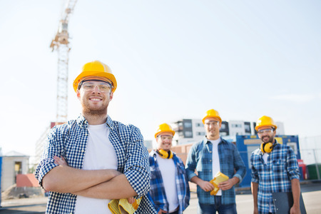 construction sites: business, building, teamwork and people concept - group of smiling builders in hardhats with clipboard outdoors Stock Photo
