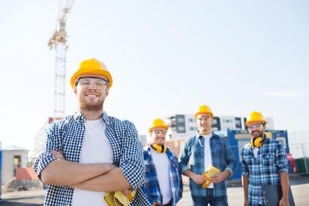 arbeiter: Geschäft, Gebäude, Teamarbeit und die Leute Konzept - Gruppe von lächelnden Bauer in Streetware mit Klemmbrett im Freien