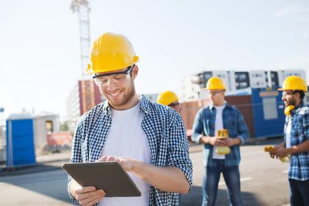 workers: negocio, construcci�n, trabajo en equipo, la tecnolog�a y el concepto de la gente - grupo de sonrientes constructores de cascos con el ordenador Tablet PC al aire libre Foto de archivo