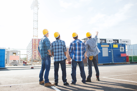 building work: business, building, teamwork and people concept - group of builders in hardhats outdoors from back Stock Photo