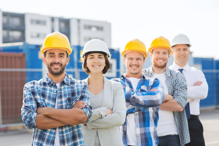 happy worker: business, building, teamwork and people concept - group of smiling builders in hardhats outdoors