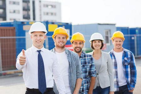 residential construction: business, building, teamwork, gesture and people concept - group of smiling builders in hardhats showing thumbs up outdoors