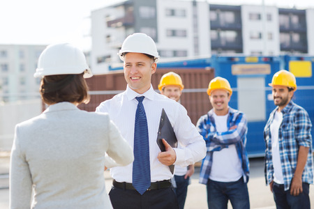 site: business, building, teamwork, gesture and people concept - group of smiling builders in hardhats with clipboard greeting each other outdoors