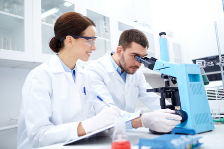 science, chemistry, technology, biology and people concept - young scientists with microscope making test or research in clinical laboratory and taking notes photo