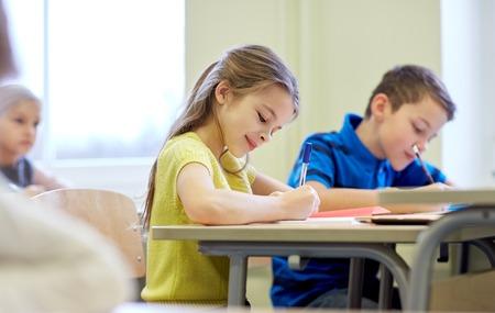 convivencia escolar: educación, escuela primaria, el aprendizaje y el concepto de la gente - grupo de niños de la escuela con lápices y cuadernos de escritura de prueba en el aula Foto de archivo
