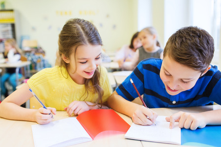children writing: education, elementary school, learning and people concept - group of school kids with pens and notebooks writing test in classroom