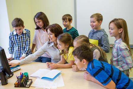 escuela primaria: educación, escuela primaria, el aprendizaje, la tecnología y el concepto de la gente - grupo de niños de la escuela con el maestro en busca de monitor de la computadora en el aula