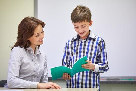 maestro: educaci�n, escuela primaria, el aprendizaje, la exploraci�n y la gente concepto - muchacho de escuela con el cuaderno y el profesor en el aula Foto de archivo
