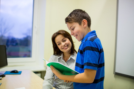 preteen boys: education, elementary school, learning, examination and people concept - school boy with notebook and teacher in classroom