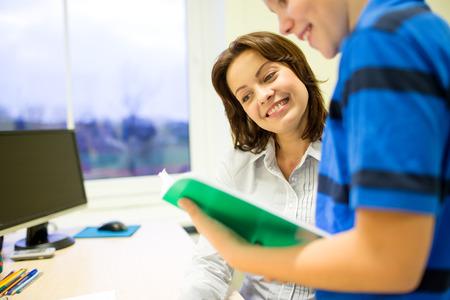 maestra: educaci�n, escuela primaria, el aprendizaje, la exploraci�n y la gente concepto - muchacho de escuela con el cuaderno y el profesor en el aula Foto de archivo