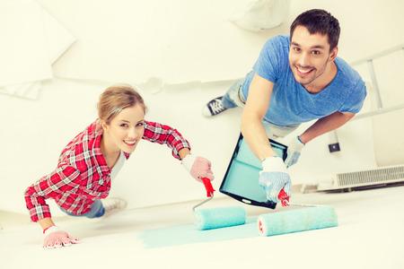reparatie, bouw en huis concept - lachende paar schilderij muur thuis Stockfoto