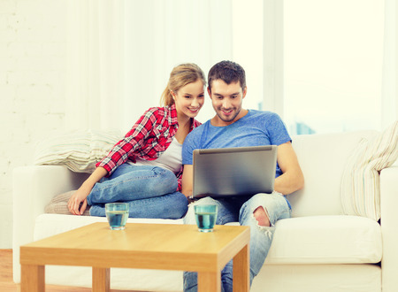 husband: home, technology and relationships concept - smiling couple with laptop computer at home