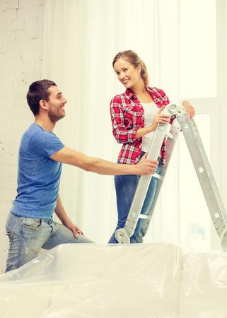 adn: reparación, renovación adn concepto de bienes raíces - sonriendo cortinas colgantes de pareja Foto de archivo