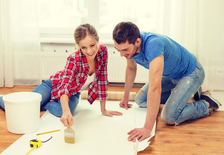 repair, building and home concept - smiling couple smearing wallpaper with glue