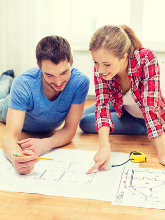floor plans: repair, building, renovation and home concept - smiling couple looking at blueprint at home