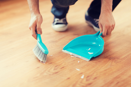 home keeping: cleaning and home concept - close up of male brooming wooden floor with small whisk broom and dustpan