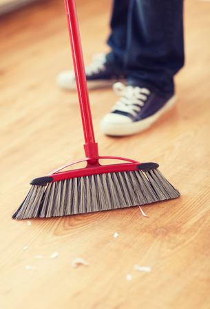 brooming: cleaning and home concept - close up of male brooming wooden floor Stock Photo