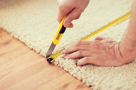 carpet flooring: repair, building and home concept - close up of male hands cutting carpet with blade