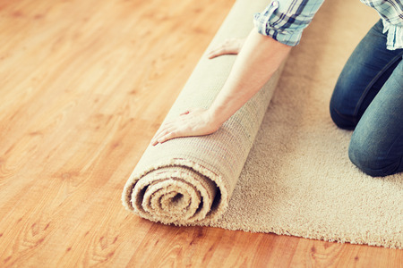 carpet and flooring: repair, building and home concept - close up of male hands unrolling carpet