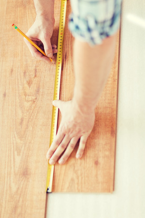 repair, building and home concept - close up of male hands measuring wood flooring photo