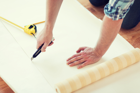 repair, building and home concept - close up of male hands cutting wallpaper photo