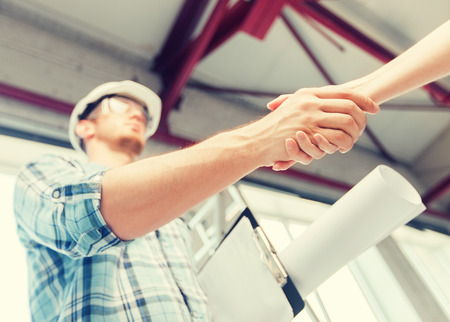 architecture and home renovation concept - builder with blueprint shaking partner hand