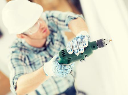 trabajando en casa: dise�o de interiores y reformas del hogar concepto - hombre en el casco con el agujero toma taladro el�ctrico en pared Foto de archivo