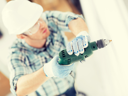 my home: interior design and home renovation concept - man in helmet with electric drill making hole in wall Stock Photo