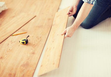 Reparación, construcción y el hogar concepto - cerca de las manos masculinas intalling pisos de madera Foto de archivo - 35794716