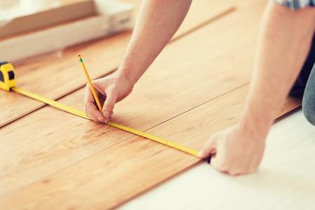 修理、建物しホーム コンセプト - 木製のフロアー リングを測定する男性の手のクローズ アップ