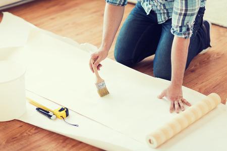 pegamento: reparación, construcción y el hogar concepto - cerca de las manos masculinas untando papel pintado con pegamento Foto de archivo