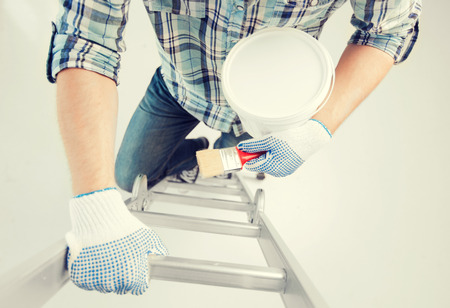interior design and home renovation concept - man with paintbrush and paint pot climbing ladder