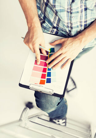 interior designer: interior design and renovation concept - man with color samples for selection