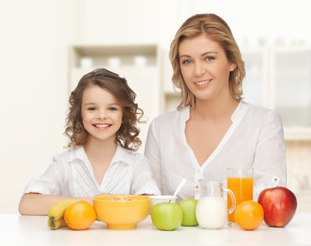 people, healthy lifestyle, family and food concept - happy mother and daughter eating healthy breakfast over home kitchen background photo