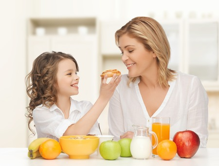 over eating: people, healthy lifestyle, family and food concept - happy mother and daughter eating healthy breakfast over home kitchen background